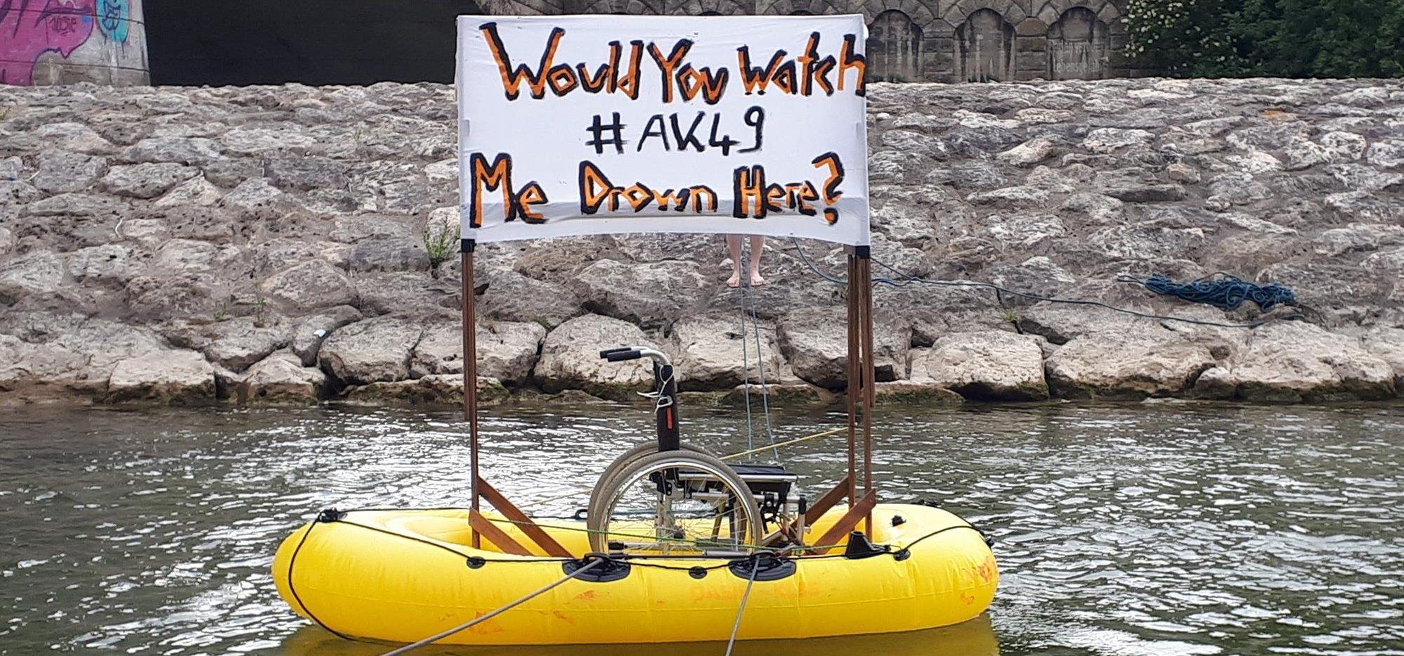 Ein Schlauchboot auf der Isar. Darin ein Rollstuhl.