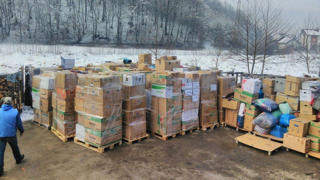 Auf vielen Paletten stehen zahlreiche Kartons. Im Hintergrund ist ein verschneiter Hügel.